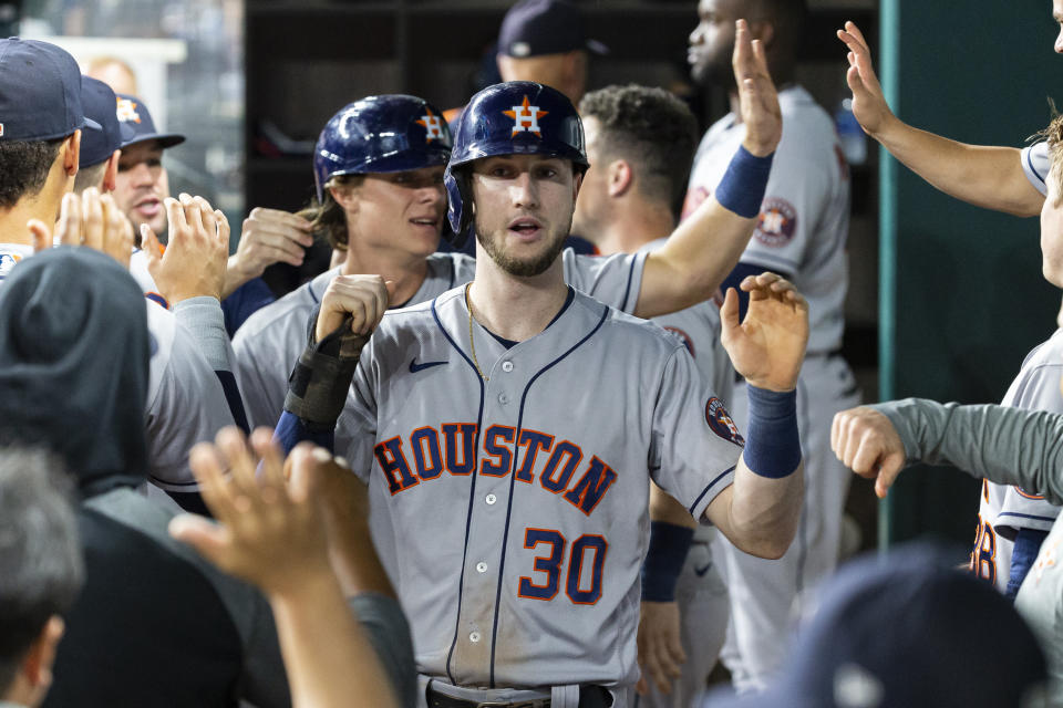 Houston Astros' Kyle Tucker (30) is congratulated by teammates after scoring a run during the seventh inning of a baseball game against the Texas Rangers, Friday, Aug. 27, 2021, in Arlington, Texas. (AP Photo/Sam Hodde)