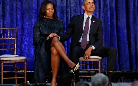 Former President Obama and first lady Michelle Obama hold hands prior to portraits unveiling at the Smithsonian's National Portrait Gallery in Washington - Credit: Reuters