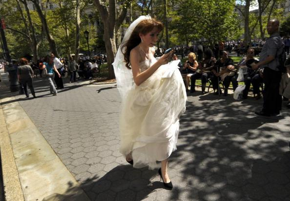 """Valeriya Shevchenko, 18, evacuated a NY courthouse during the earthquake panic but the eye-catching photo of her wedding-dress dash created complications. The young bride and groom were keeping the nuptials a secret from their disapproving families -- not such an easy feat with the highly circulated image that is now being called the """"Earthquake Bride."""" """"They'd say we're too young and not for each other. His mom is going to go crazy,"""" Shevchenko told the New York Post. The couple married later that day. (Photo: TIMOTHY A. CLARY/AFP/Getty Images)"""