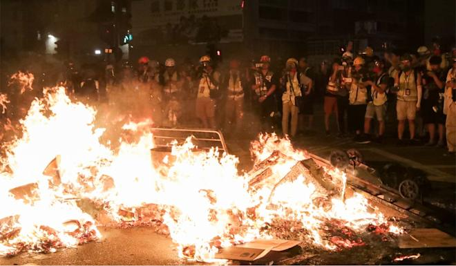 Protesters set fire to a barricade on Nathan Road near Mong Kok Police Station. Photo: Edmond So