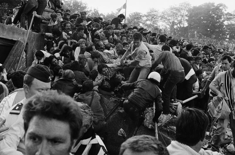 FILE - In this May 29, 1985 file photo, a crowd of soccer fans try to escape a collapsed wall prior to the start of the European Cup final between Liverpool and Juventus, at the Heysel Stadium in Brussels. Liverpool had been the dominant team in the European Cup, winning four titles between 1977 and 1984. Friday, May 29, 2020 marks 35 years since 39 victims lost their lives during a European Cup football match between Liverpool and Juventus due to a surge of rival supporters resulting in a collapsed wall. (AP Photo/Gianni Foggia, File)
