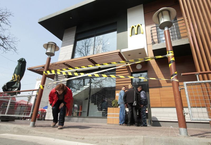 """A woman makes her way under a barrier tape outside a McDonald's restaurant, which was earlier closed for clients, in the Crimean city of Simferopol April 4, 2014. McDonald's has suspended work at its restaurants in Crimea for """"manufacturing reasons"""", the U.S. fast food chain said on Friday, the second international company to cease operations this week on the peninsula annexed by Russia. REUTERS/Stringer (UKRAINE - Tags: POLITICS BUSINESS SOCIETY)"""