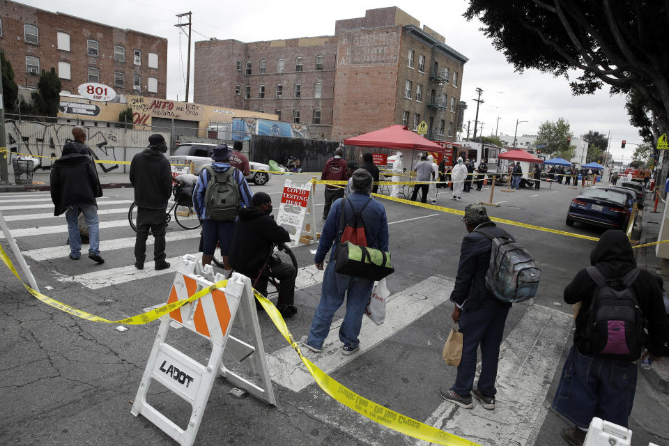 """FILE - In this April 20, 2020, file photo, people line up to take a COVID-19 test in the Skid Row district in Los Angeles. Coronavirus cases have surged to record levels in the Los Angeles area. Health officials said Wednesday, July 15, 2020, the nation's most populous county is in """"an alarming and dangerous phase"""" that if not reversed could overwhelm intensive care units and usher in more sweeping closures. The three-day average of hospital patients in the county is above 2,000 for the first time. Many indoor businesses were ordered closed Monday. County officials say testing will be expanded for people with the highest need, mainly Blacks and Hispanics in low-income communities. (AP Photo/Marcio Jose Sanchez, File)"""