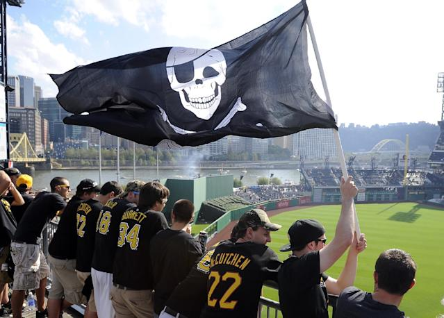 FILE - In this Oct. 3, 2013, file photo, Pittsburgh Pirates fans wave a Jolly Roger flag as they stand in the left field rotunda before Game 3 of a National League division baseball series between the Pirates and St. Louis Cardinals in Pittsburgh .(AP Photo/Don Wright, File)