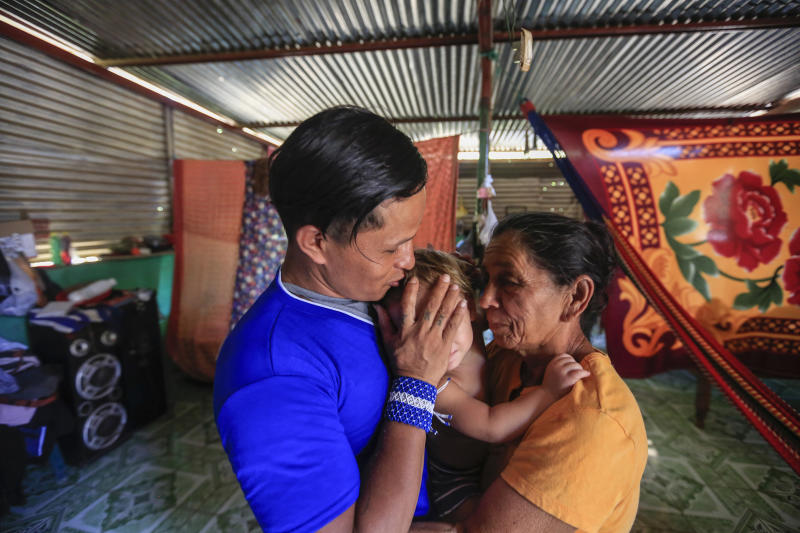 Prisoner Franklin Perez, 29, hugs his son and his mother Lidia in his home after he was released to house arrest, in Managua, Nicaragua, Friday, April 5, 2019. Perez is among the 50 people released Friday who had been jailed for protesting against President Daniel Ortega's government. However charges were not dropped against the demonstrators. Instead they were for the most part transferred to a form of house arrest, short of the unrestricted freedom that the opposition has demanded. (AP Photo/Alfredo Zuniga)