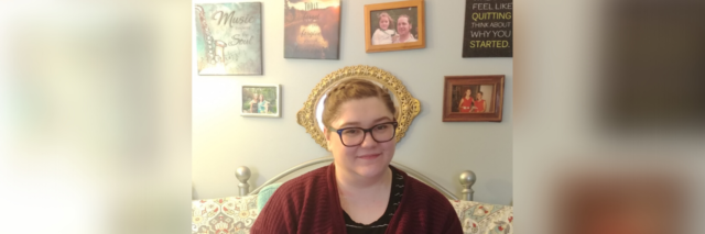 Grace sitting in bed with inspirational art on the wall behind her.