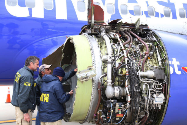 <p>National Transportation Safety Board investigators examine damage to the engine of the Southwest Airlines plane that made an emergency landing at Philadelphia International Airport in Philadelphia on Tuesday, April 17, 2018. (Photo: NTSB via AP) </p>