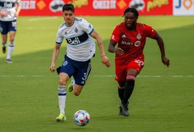 Vancouver defender Cristian Gutierrez, left, dribbles the ball past TFC forward Ayo Akinola during the Whitecaps 2-2 draw with Toronto on Saturday. (Nathan Ray Seebeck/USA TODAY Sports - image credit)