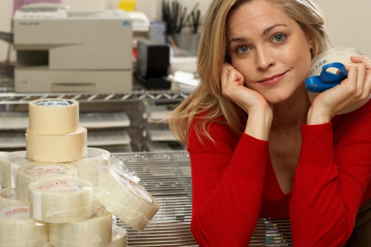Female office worker leaning on elbows by rolls of tape, portrait