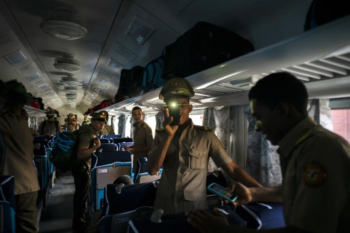 Cadets board the first train using new equipment from China, in Havana, Cuba, Saturday, July 13, 2019. The first train using new equipment from China pulled out of Havana Saturday, hauling passengers on the start of a 915-kilometer (516-mile) journey to the eastern end of the island as the government tries to overhaul the country's aging and decrepit rail system. (AP Photo/Ramon Espinosa)