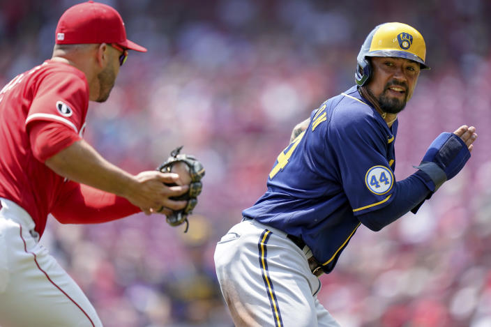 Milwaukee Brewers' Jace Peterson (14) is caught in a rundown by Cincinnati Reds third baseman Eugenio Suarez (7) during the first inning of a baseball game in Cincinnati, Sunday, July 18, 2021. (AP Photo/Bryan Woolston)