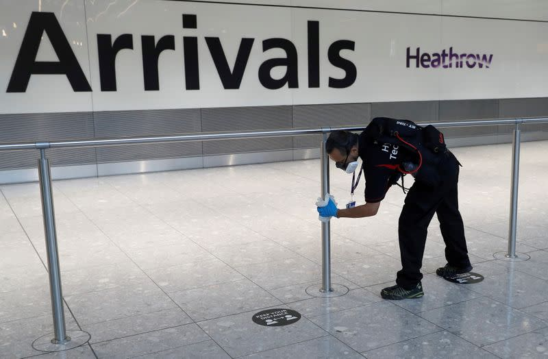 FILE PHOTO: A worker sanitises a barrier at the International arrivals area of Terminal 5 in London's Heathrow Airport