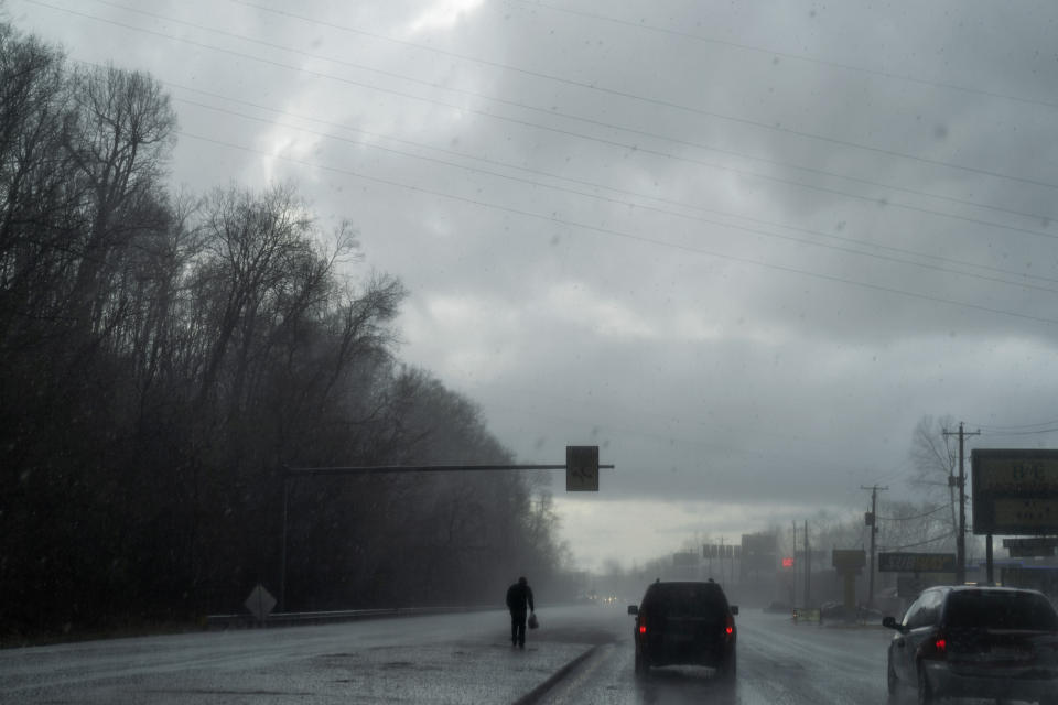 A man walks through a hail storm as the Quick Response Team's vehicle drives to visit another client who recently overdosed, Thursday, March 18, 2021, in Huntington, W.Va. Huntington was once ground-zero for this epidemic. Several years ago, they formed the team that within days visits everyone who overdoses to try to pull them back from the brink. It was a hard-fought battle, but it worked. The county's overdose rate plummeted. They wrestled down an HIV cluster. They finally felt hope. Then the pandemic arrived and it undid much of their effort: overdoses shot up again, so did HIV diagnoses. (AP Photo/David Goldman)
