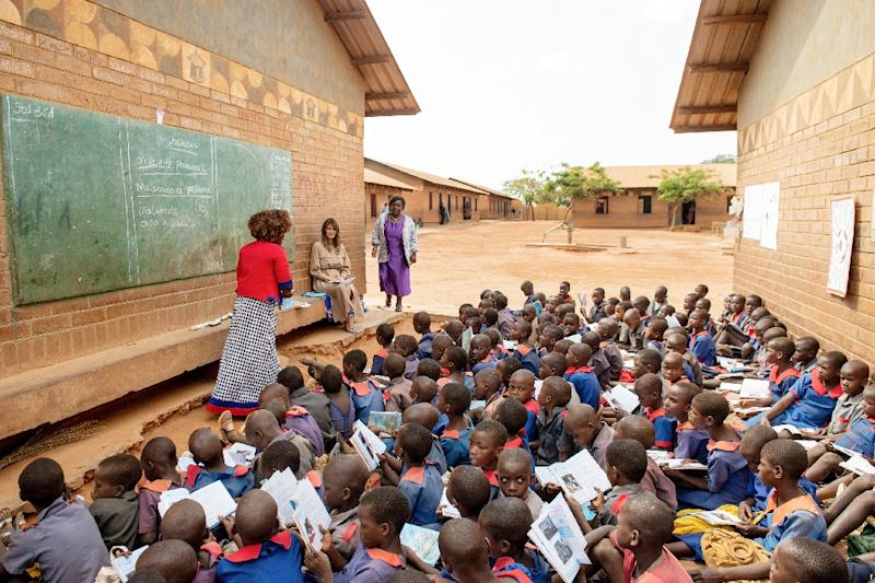 At a Lilongwe primary school US First Lady Melania Trump watched dozens of pupils sitting on the ground in the sun as a teacher taught on a blackboard on the side of a building