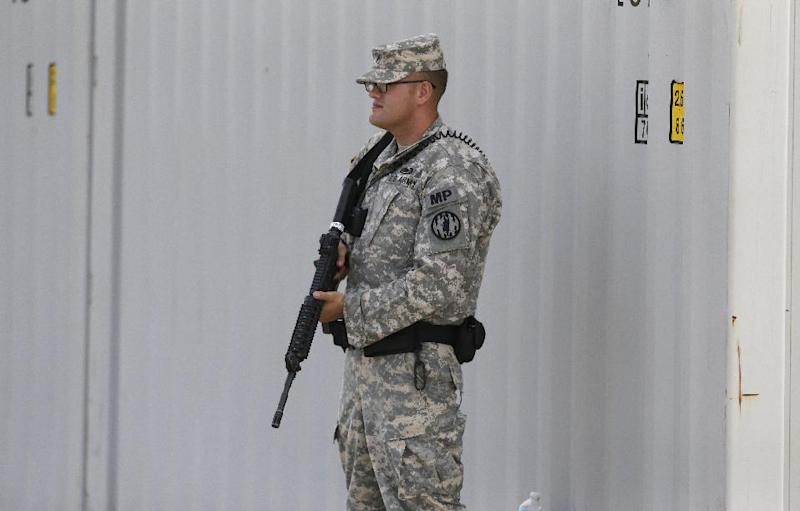 An armed soldier stands guard along a security barrier outside the courthouse holding the the court martial of Maj. Nidal Malik Hasan Friday, Aug. 23, 2013, in Fort Hood, Texas. Military jurors are deliberating for a verdict against Hasan, on trial for the 2009 shooting rampage at Fort Hood. (AP Photo/LM Otero)