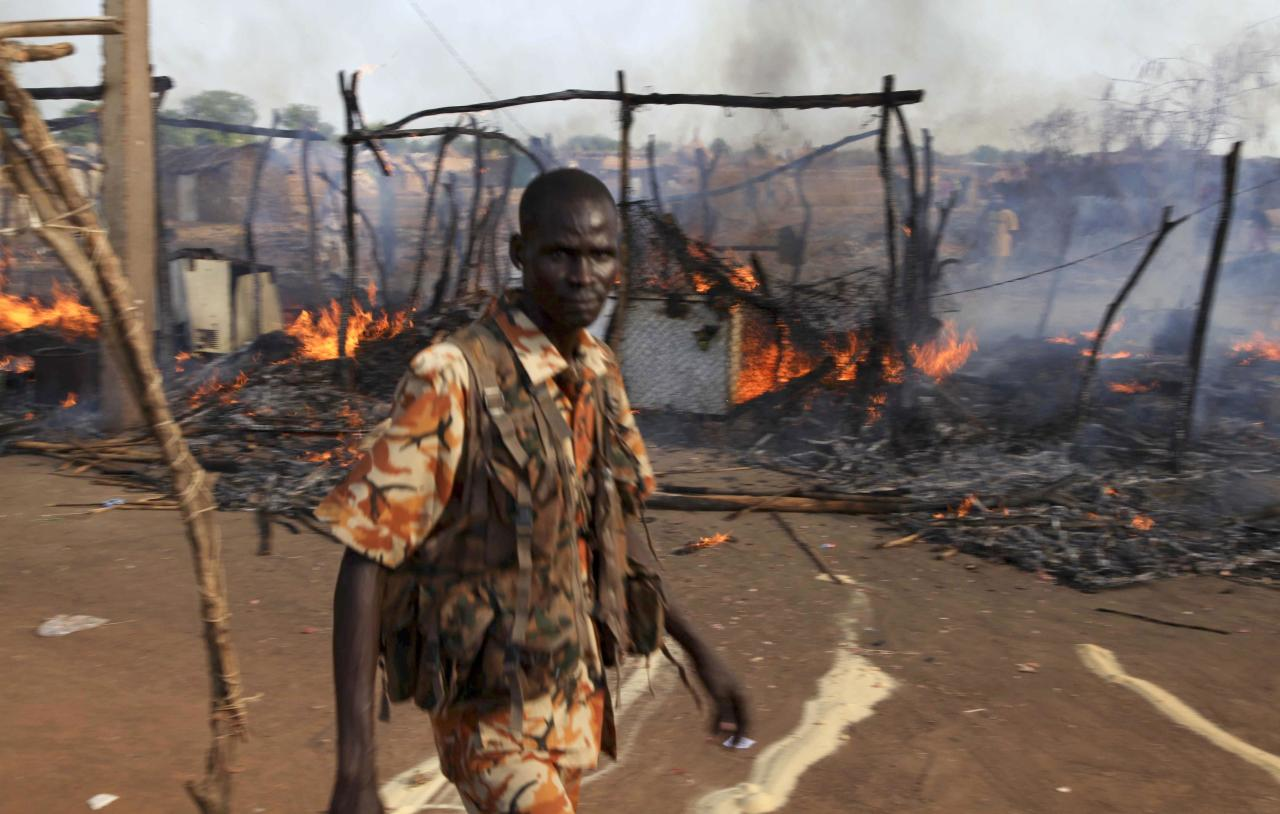 A policeman walks past the smoldering remains of a market in Rubkona near Bentiu in South Sudan, Monday, April 23, 2012. A boy was killed and at least two people were wounded Monday when Sudanese aircraft bombed an area near the town of Bentiu in South Sudan, an official and witness said, increasing the threat of a full-scale war breaking out between the two nations. (AP Photo/Michael Onyiego)