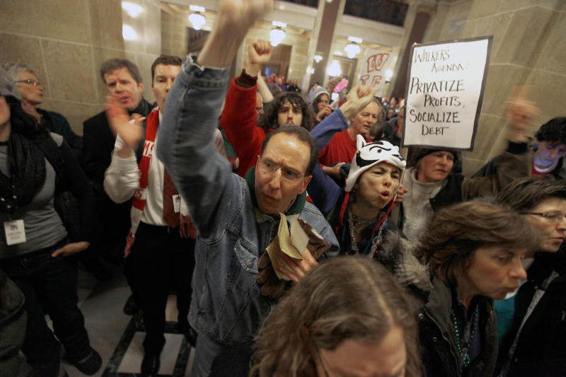 Opponents of Wisconsin Governor Scott Walker's budget repair bill, including C.J. Terrell demonstrate outside the senate parlor at the Wisconsin State Capitol Building as legislators inside voted to move forward on an amended version of the controversial bill Wednesday, March 9, 2011. The new bill removes the fiscal elements from the bill and strips public employees of collective bargaining rights. (AP Photo/Wisconsin State Journal, John Hart)