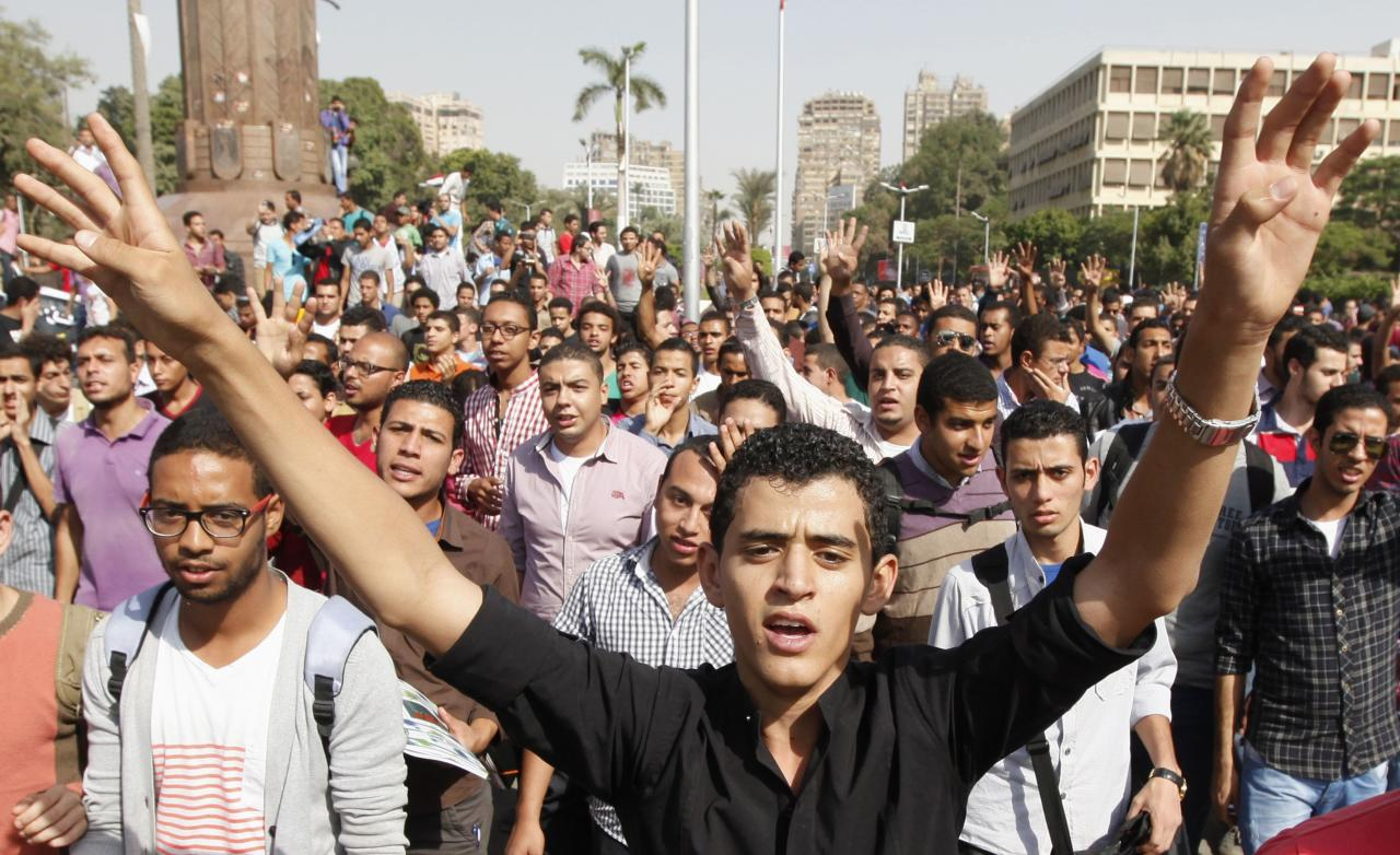 """Cairo university students and members of the Muslim Brotherhood shout slogans against the military in front of Cairo University in Cairo, October 8, 2013. Hundreds of Muslim Brotherhood supporters chanted """"Down with the military government"""" outside Cairo University on Tuesday, defying Egypt's army-backed authorities despite deadly clashes with security forces two days earlier. REUTERS/Mohamed Abd El Ghany (EGYPT - Tags: POLITICS EDUCATION CIVIL UNREST)"""