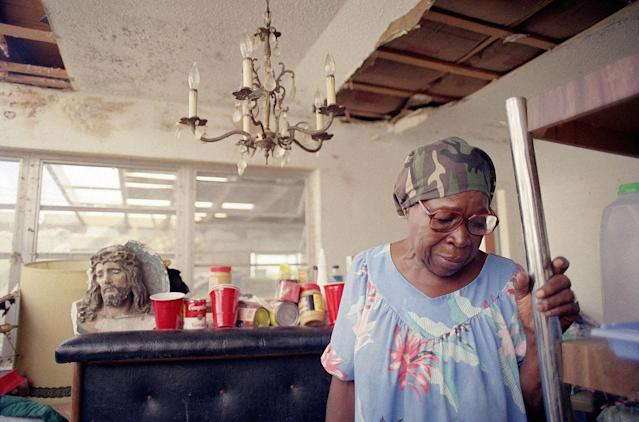 <p>Florida City, Fla., resident Doloris Clark, 74, refuses to leave her home which was badly damaged by Hurricane Andrew, fearing that thieves would take her remaining belongings, Sept. 6, 1992. A bust of Christ sits in the background. (AP Photo/John Moore) </p>