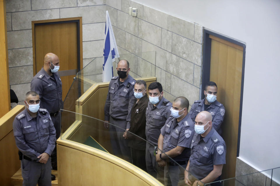 Yakub Kadari is surrounded by guards as they stand in a courtroom in Nazareth, Israel, after he and three other Palestinian fugitives were captured on Saturday, Sept. 11, 2021. Israeli police on Saturday said they have arrested four of the six Palestinians who broke out of a maximum-security prison this week — including a famed militant leader whose exploits over the years have made him a well-known figure in Israel. (AP Photo/Sebastian Scheiner)