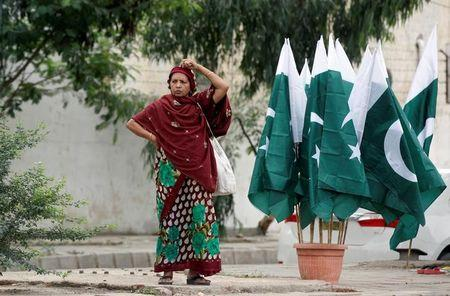 A woman adjusts her scarf as she waits for a bus next to a stall with national flags, ahead of Pakistan's Independence Day, in Karachi