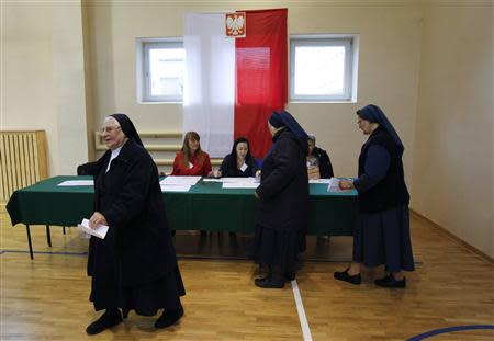 A Catholic nun walks with a ballot paper before casting her vote at a polling station in Warsaw