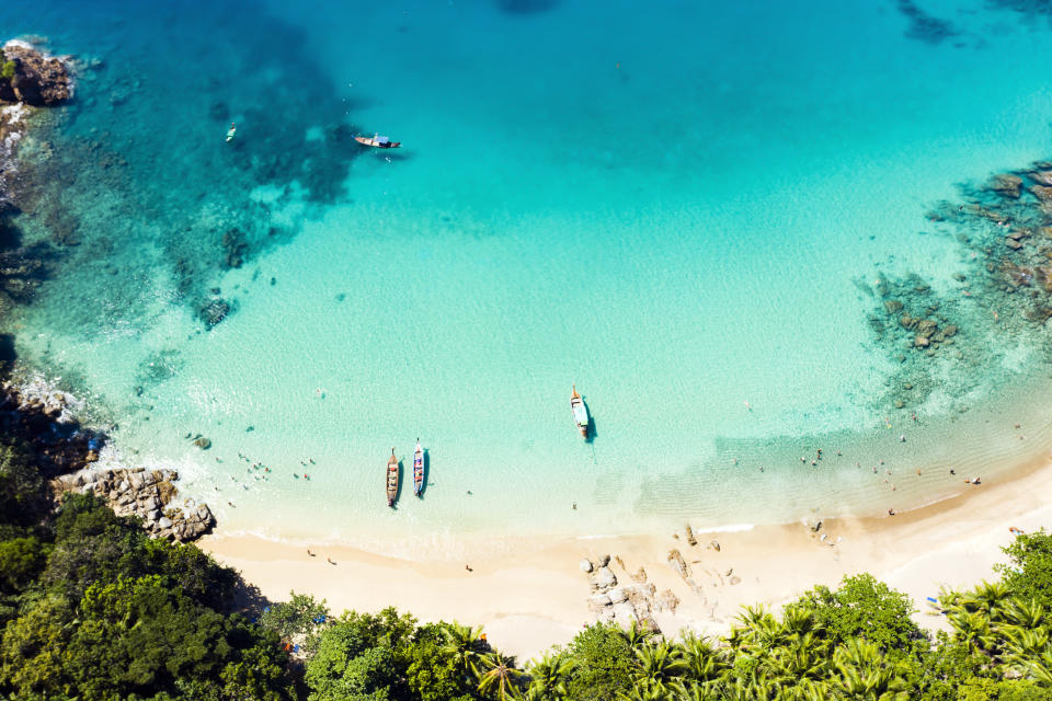 View from above, stunning aerial view of a beautiful tropical beach with white sand and turquoise clear water, long-tail boats and people sunbathing, Banana beach, Phuket, Thailand.