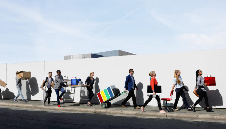 Office workers walking in a line down street carrying office equipment