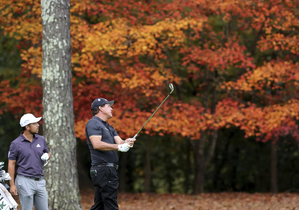 Xander Schauffele, left, watches Phil Mickelson's fairway shot to the 11th green during a practice round for the Masters golf tournament at Augusta National Golf Club in Augusta, Ga., Tuesday, Nov 10, 2020. (Curtis Compton/Atlanta Journal-Constitution via AP)