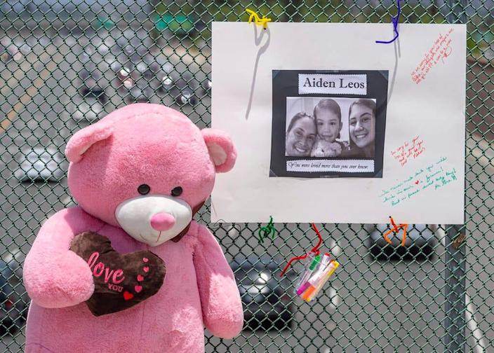 A large stuffed toy bear and a poster board adorned by a photo and notes are part of a memorial on an overpass in Orange, Calif., for Aiden Leos, 6, who was shot and killed during a road rage attack.