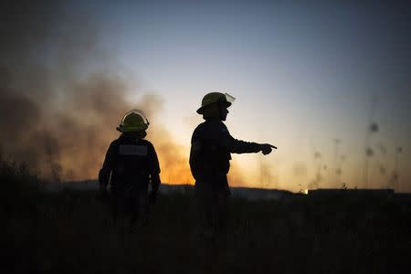 Israeli firefighters monitor a fire caused by a rocket fired from the Gaza Strip by Palestinian militants, near Sderot