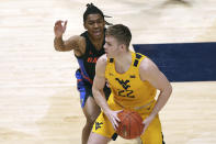 West Virginia guard Sean McNeil (22) is defended by Florida guard Ques Glover (0) during the first half of an NCAA college basketball game Saturday, Jan. 30, 2021, in Morgantown, W.Va. (AP Photo/Kathleen Batten)