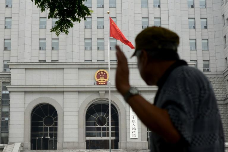 A man walks past a courthouse in Beijing during the sentencing of China's former railways minister Liu Zhijun on July 8, 2013, who was given a suspended death penalty for taking bribes worth 60 million yuan