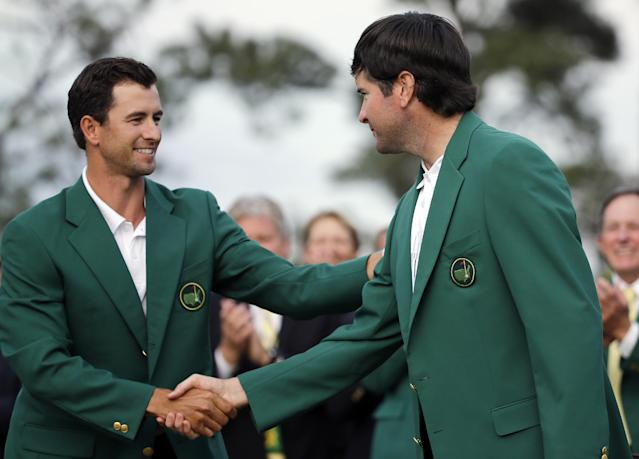 Defending Masters' champion Adam Scott, of Australia, shakes hands with Bubba Watson, right, after presenting him with his green jacket after winning the Masters golf tournament Sunday, April 13, 2014, in Augusta, Ga. (AP Photo/David J. Phillip)