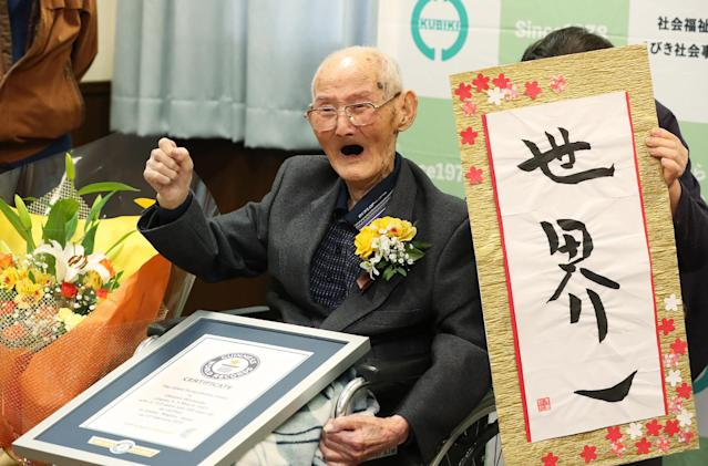 Chitetsu Watanabe, aged 112, poses next to the calligraphy reading in Japanese 'World Number One' after he was awarded as the world's oldest living male (Getty)