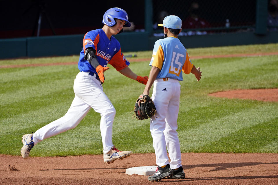 Taylor, Mich.'s Cameron Thorning, left, is greeted by Honolulu, Hawaii shortstop Kekoa Payanal (15) as he rounds second after hitting a two-run home run off starting pitcher Micah Bennett during the first inning of a baseball game at the Little League World Series in South Williamsport, Pa., Saturday, Aug. 28, 2021. (AP Photo/Tom E. Puskar)