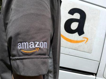FILE PHOTO: An Amazon.com Inc driver stands next to an Amazon delivery truck in Los Angeles
