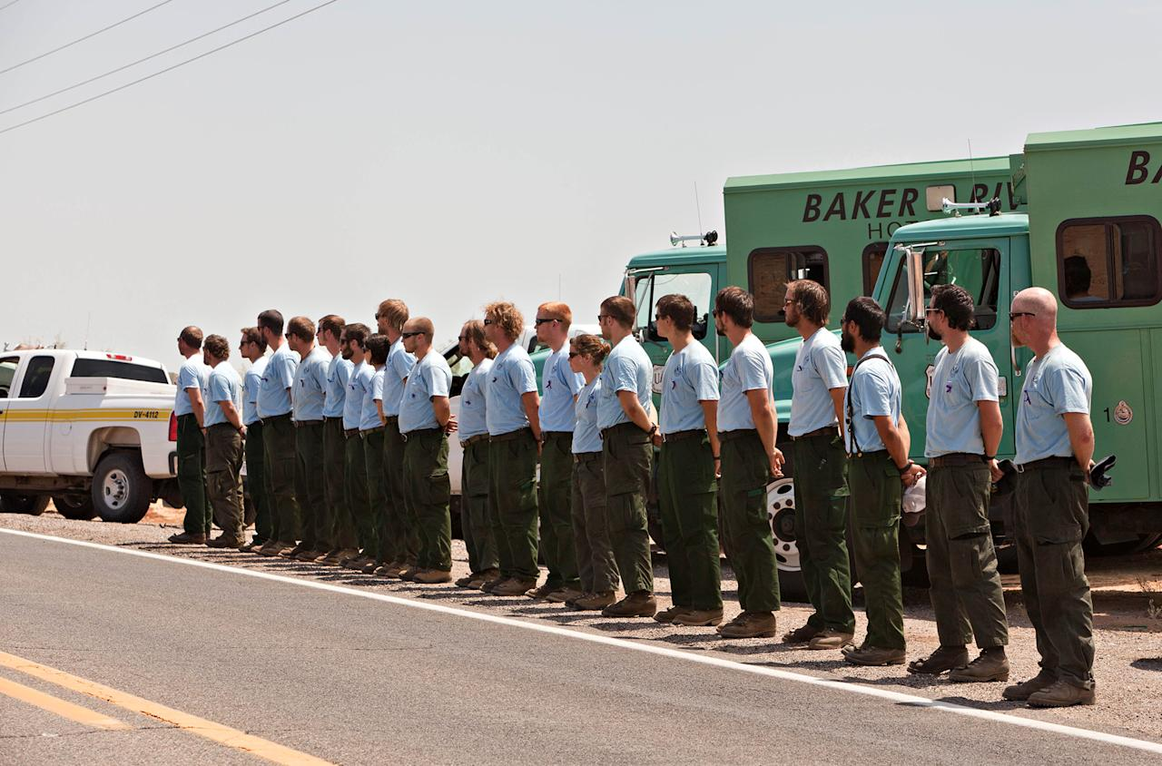 Members of the Baker River Hotshots from Sedro Wooley, Washington and Bureau of Land Management fire personnel lined Highway 89, by the BLM's Mohave Mountain Fire Center-north of Wickenburg, Ariz to honor the fallen members of the Granite Mountain Hotshot Crew as the bodies of the 19 firefighters were returned to Prescott, Ariz., Sunday, July 7, 2013 from Phoenix. All, save one, of the crew perished fighting the Yarnell Hill Fire on June 28, 2013. (AP Photo/The Arizona Republic, Tom Story)
