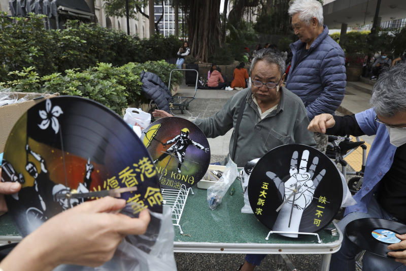 Hong Kong men prepare protest themed clocks made from vinyl records ahead of a rally demanding electoral democracy and call for boycott of the Chinese Communist Party and all businesses seen to support it in Hong Kong, Sunday, Jan. 19, 2020. Hong Kong has been wracked by often violent anti-government protests since June, although they have diminished considerably in scale following a landslide win by opposition candidates in races for district councilors late last year. (AP Photo/Ng Han Guan)