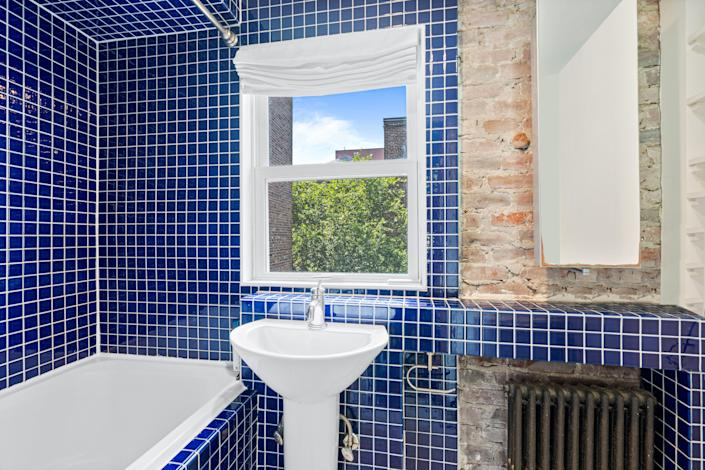 A bathroom with small blue tiling and a window above the sink