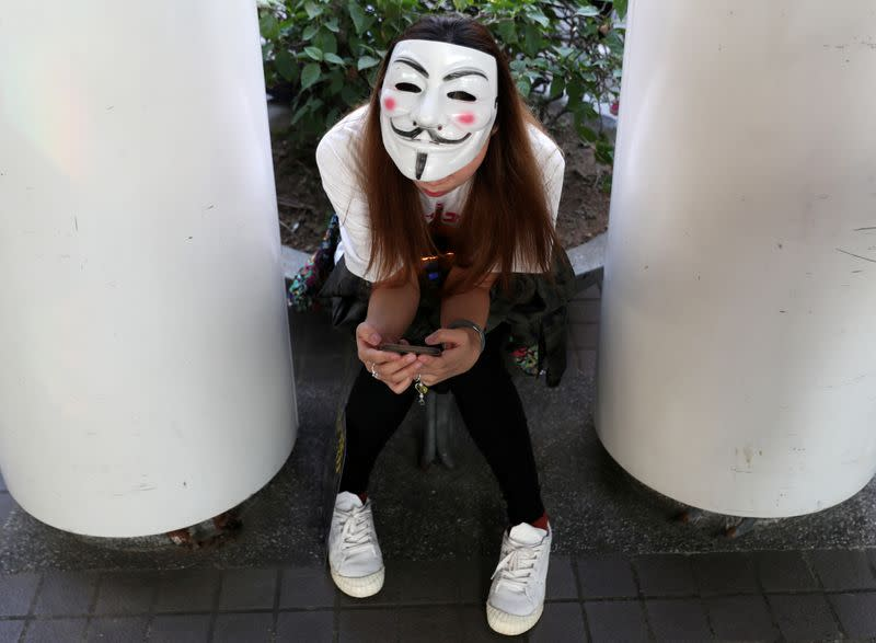 "FILE PHOTO: An anti-government protester wearing a Guy Fawkes mask checks her phone during the ""Lest We Forget"" rally in Hong Kong"