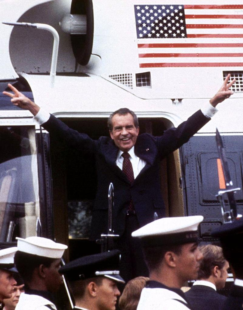 Following his resignation, U.S. President Richard M. Nixon flashes the V-for-victory sign as he boards his Marine One helicopter for the last time on the South lawn of the White House, Aug. 9, 1974.  (Photo: STR New / Reuters)