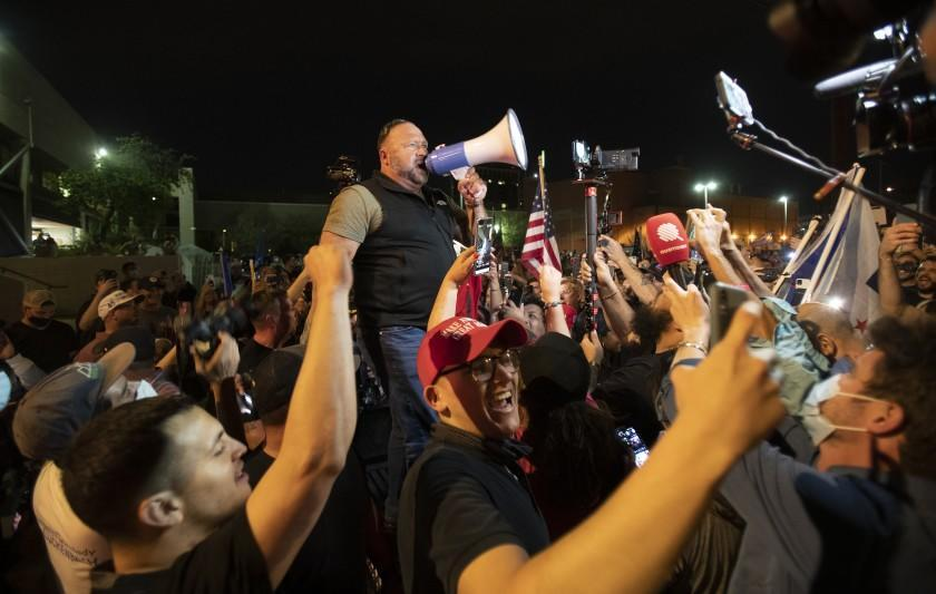 PHOENIX, AZ - NOVEMBER 5, 2020: Far-right radio host and conspiracy theorist Alex Jones rallies the crowd of Trump supporters who have been protesting in the parking lot at the Maricopa County Tabulation and Election Center as ballots continue to be counted inside the building on November 5, 2020 in Phoenix, Arizona (Gina Ferazzi / Los Angeles Times)