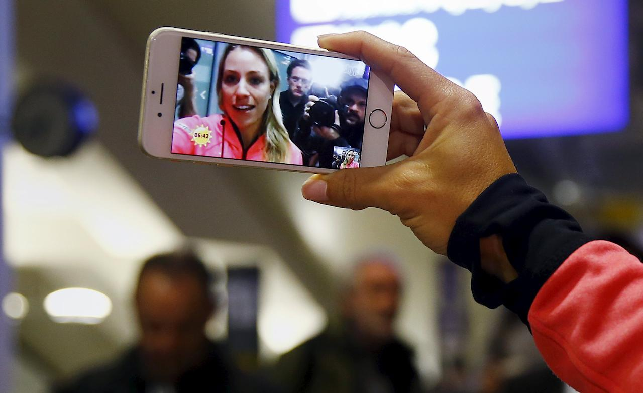 Australian Open winner Angelique Kerber of Germany uses her mobile phone to conduct a live television interview after her arrival at the airport in Frankfurt, Germany