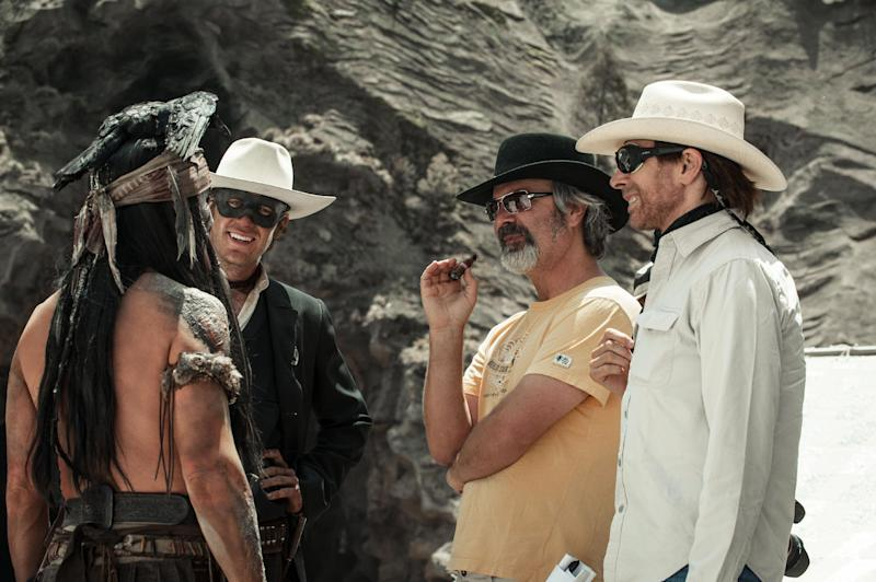 """This undated publicity photo released by Disney/Bruckheimer Films shows, from left, Johnny Depp as Tonto, Armie Hammer as The Lone Ranger, director, Gore Verbinski and producer, Jerry Bruckheimer, on the set of """"The Lone Ranger."""" The film opens nationwide on July 3, 2013. (AP Photo/Disney/Bruckheimer Films, Peter Mountain)"""