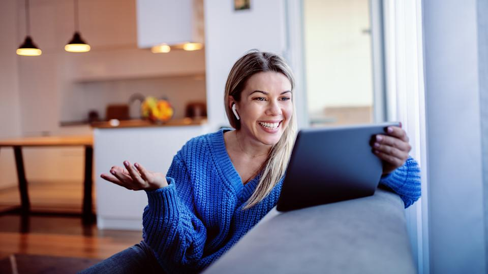Gorgeous smiling caucasian young blonde in blue sweater and in jeans sitting on sofa and using tablet for video call.