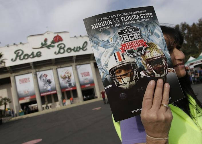 In this Jan. 6, 2014, file photo, a vendor sells a program outside the Rose Bowl before the BCS National Championship NCAA college football game between Auburn and Florida State in Pasadena, Calif. (AP Photo/Chris Carlson, File)