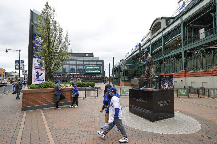 CORRECTS YEAR TO 2021-Fans walk outside the Wrigley Field as a baseball game between the Chicago Cubs and Los Angels Dodgers has been postponed due to the forecast of inclement weather, Monday, May 3, 2021, in Chicago. (AP Photo/Kamil Krzaczynski)