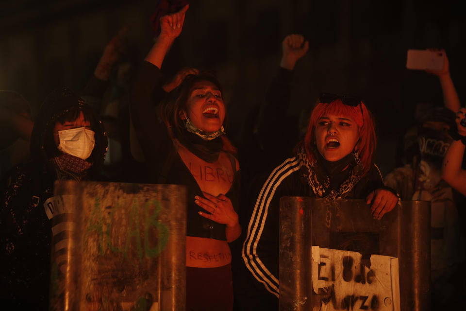 Women demonstrators chant slogans as they hold shields they ripped away from police officers hands in clashes in front of the National Palace during a march to commemorate International Women's Day and protesting against gender violence, in Mexico City, Monday, March 8, 2021. (AP Photo/Rebecca Blackwell)