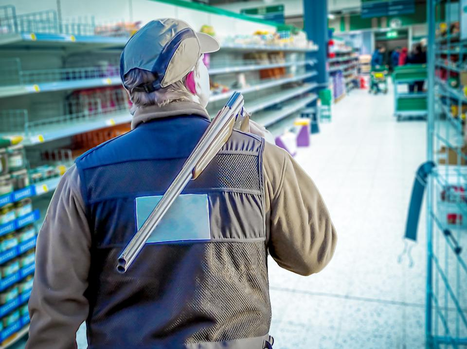 man walking with a gun at the market. Armed shop Robbery with shotgun in store. holding weapon during quarantine. panic during Virus pandemic or Infection Of Covid 19. Copy space. Filtered image